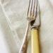 Vintage knife and fork on linen napkin. Bone-handled knife and tarnished silver fork.